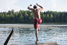 Mature Man In Red Swimming Clothes Jumping Into Lake.