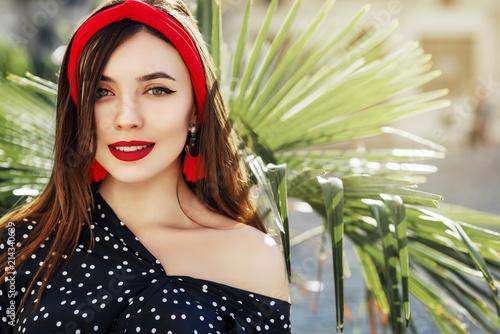 Valokuvatapetti Outdoor close up portrait of young beautiful fashionable happy woman wearing stylish red headband, tassel earrings, polka dot blouse, posing in street under palms