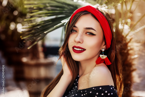 Outdoor close up portrait of young beautiful fashionable happy woman wearing stylish red headband, tassel earrings, polka dot blouse, posing in street under palms Wallpaper Mural
