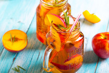 Peach Ice Tea  Fresh Mint Rosemary Wooden Background