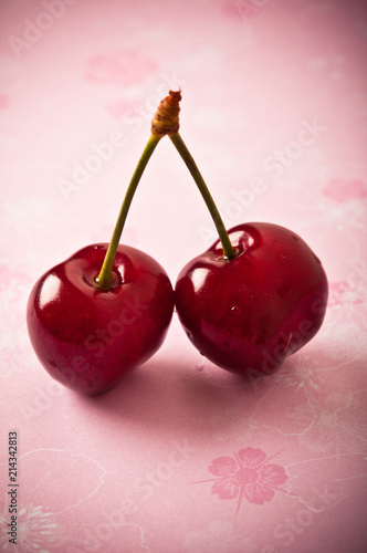 Foto op Canvas Opspattend water two cherries cherry over pink background with copy space
