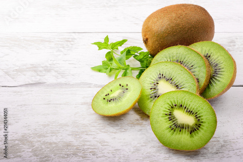 Green kiwi and mint leaves on white wood background with space for text