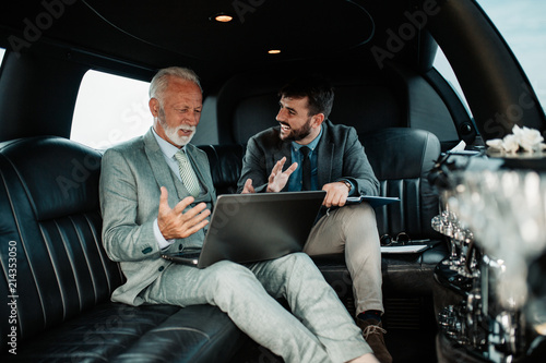 Stampa su Tela Senior businessman and his assistant sitting in limousine and celebrating their job success