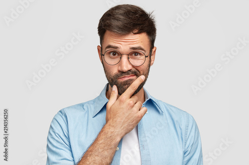 Fotografía Image of hesitant unshaven European male with thick beard, holds chin, purses lips with clueless expressions, doubts what to eat delicious for supper, isolated over white background