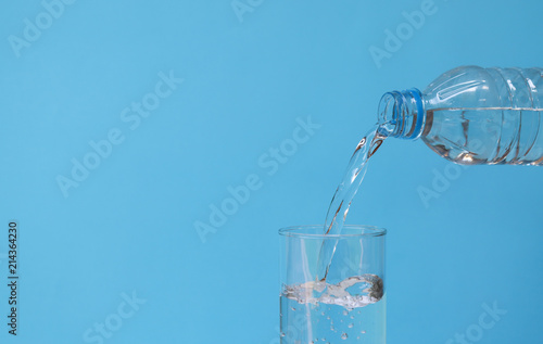 Staande foto Water Pouring mineral drinking water from bottle into glass with blue background.