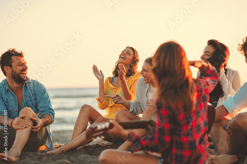 Fototapeta Happy friends sitting on the beach singing and playing guitar during the sunset obraz