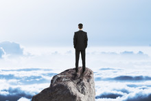 Businessman On Rock Above Clouds