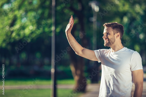 Side view of delighted male standing outdoors and waving hand to his friend Wallpaper Mural