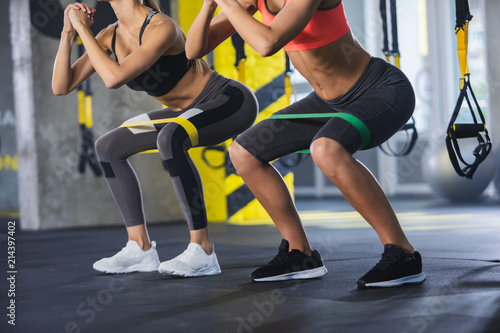 Fotografia Close up of athletic women in squat together in gym