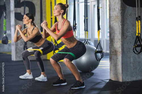 Fotografía  Two smiling athletic girls are squatting synchronously with outfit in fitness studio