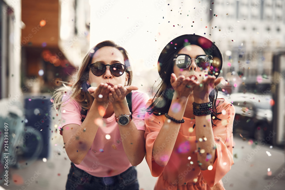 Fototapeta Portrait of cheerful ladies blowing confetti from hands. They situating on street during sunny day. Glad girl having fun, celebration concept