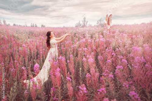 Fotografie, Obraz  Woman with owl at field of pink flowers.