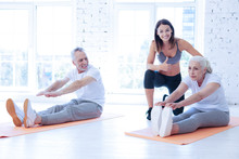 That Is Great. Concentrated Elderly Woman Sitting On The Mat And Touching Sneakers While Stretching Back
