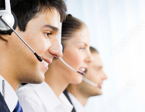 Three customer support phone operators - Buy this stock photo and