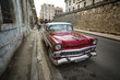 Red old american classical car in road of old Havana (Cuba)