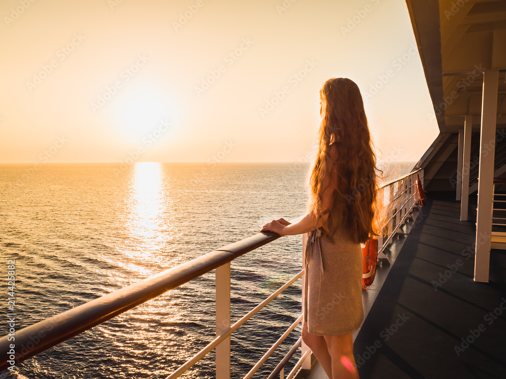 Fototapety, obrazy: Stylish, beautiful woman on an empty deck of a cruise ship against a background of sea waves, blue sky and sunset
