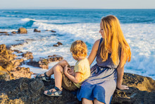 Mom And Son Are Sitting On A Rock And Looking At The Sea. Portrait Travel Tourists - Mom With Kids. Positive Human Emotions, Active Lifestyles. Happy Young Family On Sea Beach