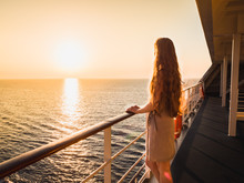 Stylish, Beautiful Woman On An Empty Deck Of A Cruise Ship Against A Background Of Sea Waves, Blue Sky And Sunset
