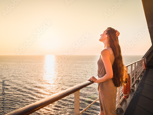 Fotografie, Obraz  Stylish, young woman on an empty deck of a cruise ship against a background of s