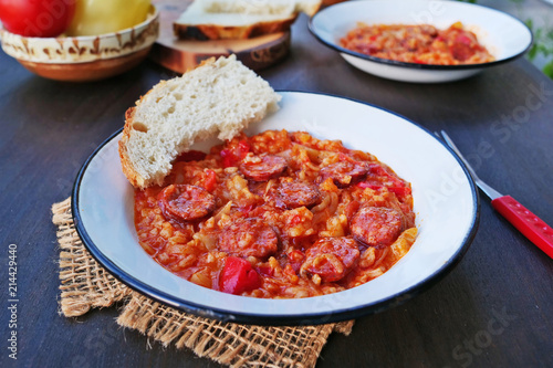 Vegetable stew, lecho with spicy sausage and rice in vintage enamel plates over dark wooden table