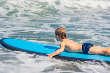 Happy Baby Boy - Young Surfer Ride On Surfboard With Fun On Sea Waves. Active Family Lifestyle, Kids Outdoor Water Sport Lessons And Swimming Activity In Surf Camp. Summer Vacation With Child