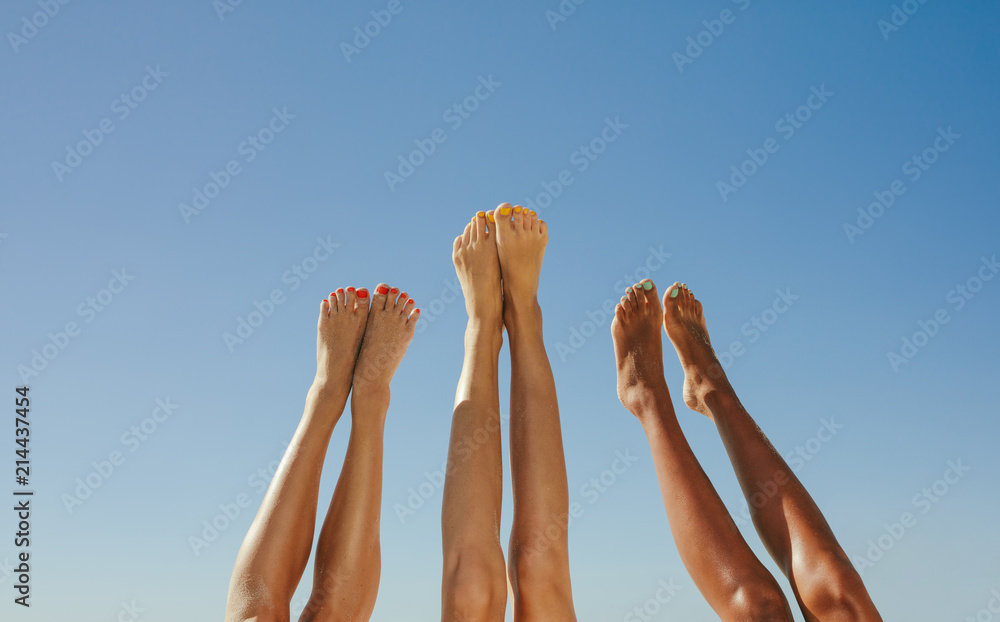 Fototapety, obrazy: Close up of legs of three women raised up in the air