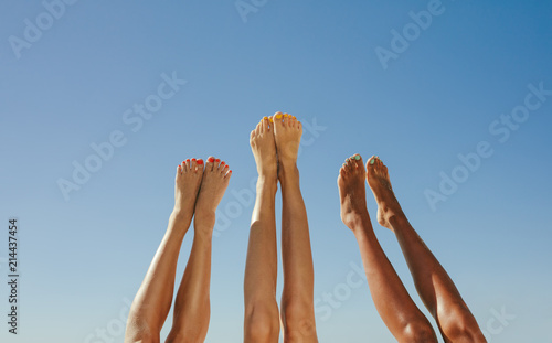 Obraz Close up of legs of three women raised up in the air - fototapety do salonu
