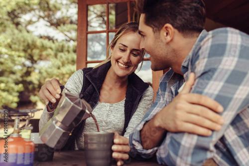 Fotografia  Woman serving coffee to her boyfriend in morning
