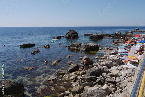 Foto op Canvas Kust Tourists, resting on the beach next to the large stone boulders, going far into the sea