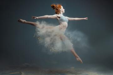 Ples u konceptu brašna. Crvenokosa ljepotica ženska djevojka odrasla žena plesačica u prašini / magli Djevojka nosi bijeli gornji dio i kratke hlačice čineći plesni element u oblaku brašna u obliku suknje na izoliranoj sivoj pozadini