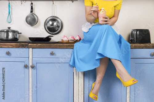Fotografia Retro pin up girl woman female housewife wearing colorful top, skirt and white apron holding cooked sweet strawberry milkshake sitting in the kitchen with utensils and tray with cupcakes
