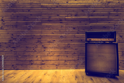 Fotografia Guitar amplifier on wooden wall and floor, music studio