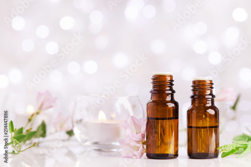 Fotografie, Obraz  Two bottles with essential oil, flowers and candles on white table with bokeh effect