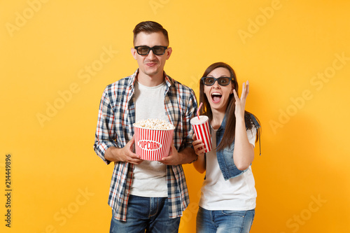 Photo  Young funny couple woman man in 3d glasses watching movie film on date holding bucket of popcorn plastic cup of soda or cola spreading hands isolated on yellow background