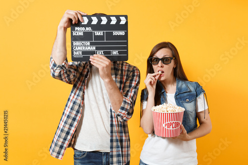 Young couple woman man in 3d glasses watching movie film on date covering face with classic black film making clapperboard eating popcorn from bucket isolated on yellow background Canvas Print
