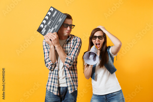 Photo  Young irritated couple woman man in 3d glasses watching movie film on date hold classic black film making clapperboard screaming on megaphone isolated on yellow background