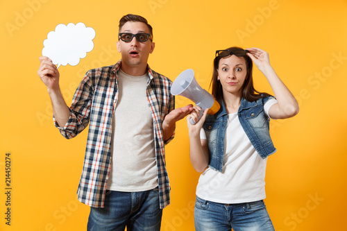 Photo  Young concerned couple woman man in 3d glasses watching movie film on date holding megaphone and say cloud with place for text, copy space isolated on yellow background