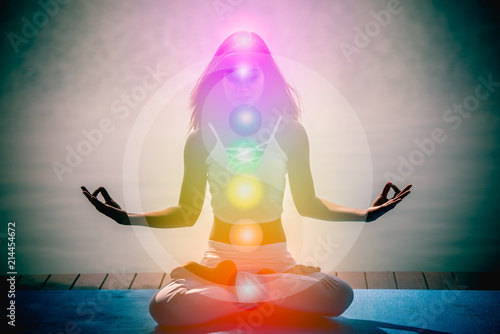 Leinwand Poster Young woman in yoga meditation with seven chakras and Yin Yang symbols