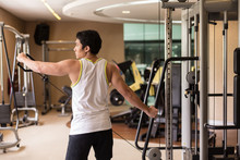 Rear View Of A Strong Young Man Lifting Cable With Single Arm, While Exercising Lateral Or Side Raise For Shoulder Muscles In A Modern Fitness Club