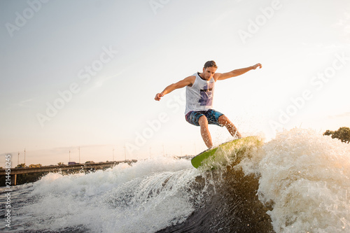 Poster Nautique motorise Young active man riding on the wakeboard