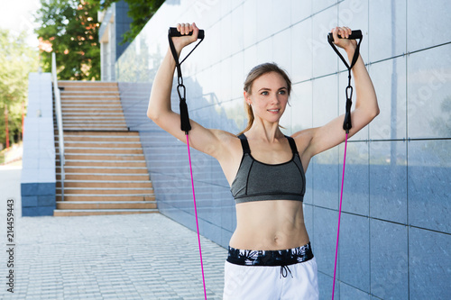 Stampa su Tela One caucasian woman  working out with resistance bands outdoors, urban style