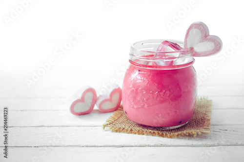 Foto op Plexiglas Milkshake Pink milkshake with heart shape marshmallows on wood background