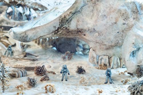 Photo of toy astronauts, giant skulls, smoke and sand Canvas-taulu