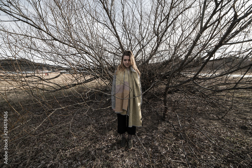 Fotografía  Young woman under the dark shadow of a tree with many branches that produces a s