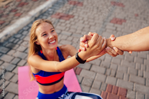 Fotografiet  Male helps a beautiful sportive woman to get up after doing a sport exercise on carpet