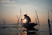 Fisherman Is Fishing In The Lake During Sunset In Thailand.
