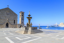 Fountain In Madraki Port With Evangelismos Chuch And Clock Tower In Rhodes, Dodecanese, Greece