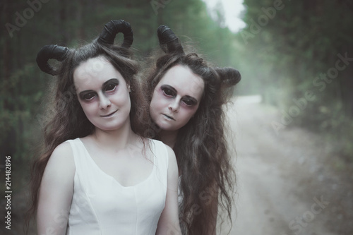 Canvas Print Two twins demons with horns in forest
