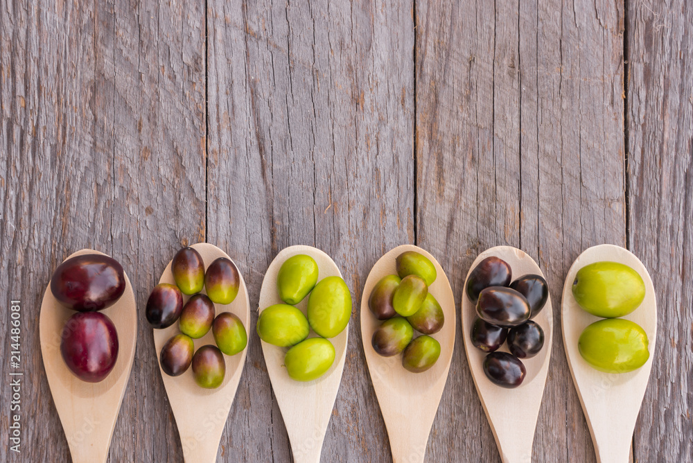 Fototapety, obrazy: Different types of olives on wooden spoons