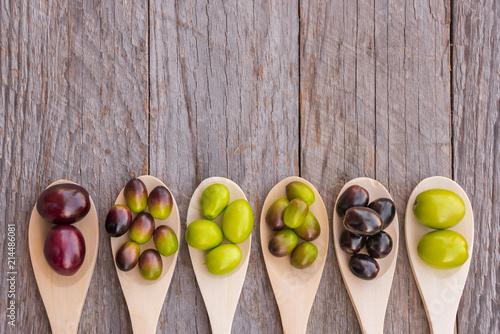Different types of olives on wooden spoons
